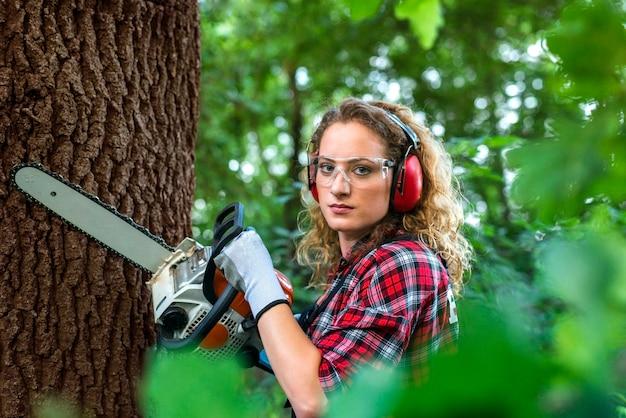 전기 톱으로 참나무 줄기를 자르는 숲의 전문 등심 무료 사진