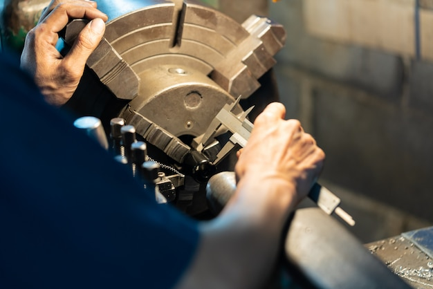 Professional machinist : man operating lathe grinding machine Premium Photo