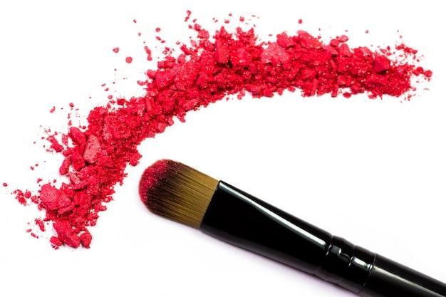 Профессиональная кисточка для макияжа на красных измельченных тенях для век Premium Фотографии