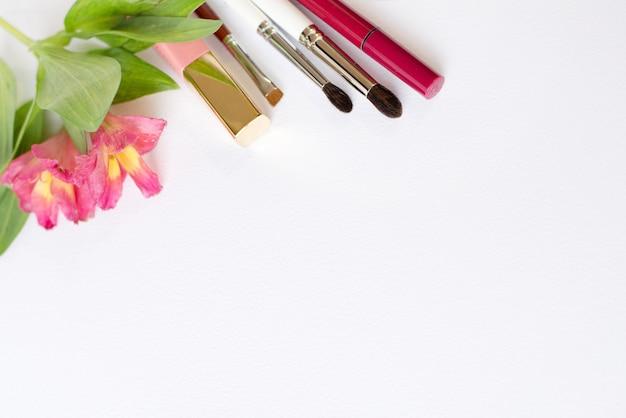 전문 메이크업 화장품, 흰색 배경에 꽃과 평평한 구성 프리미엄 사진