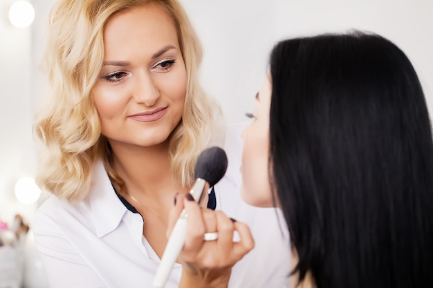 Professional makeup artist applying lipstick Premium Photo