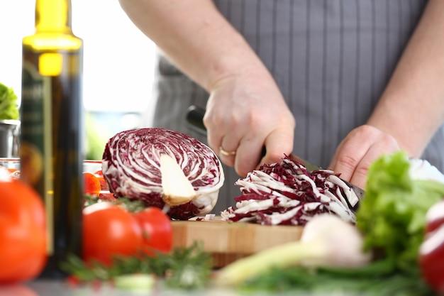 Профессиональный шеф-повар-мужчина нарезает фиолетовую капусту Premium Фотографии