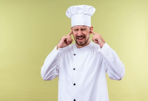 Профессиональный шеф-повар-мужчина в белой форме и поварской шляпе, закрывающей уши с раздраженным выражением лица от шума громкого звука, стоящего на зеленом фоне Бесплатные Фотографии