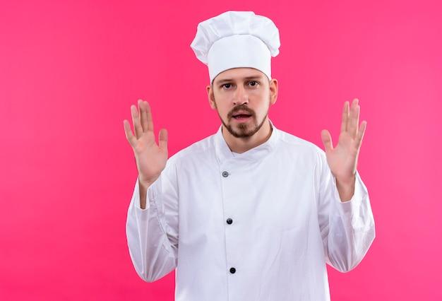 Профессиональный шеф-повар-мужчина в белой униформе и поварской шляпе, жестикулирующей руками, показывающими размер, символ измерения на розовом фоне Бесплатные Фотографии