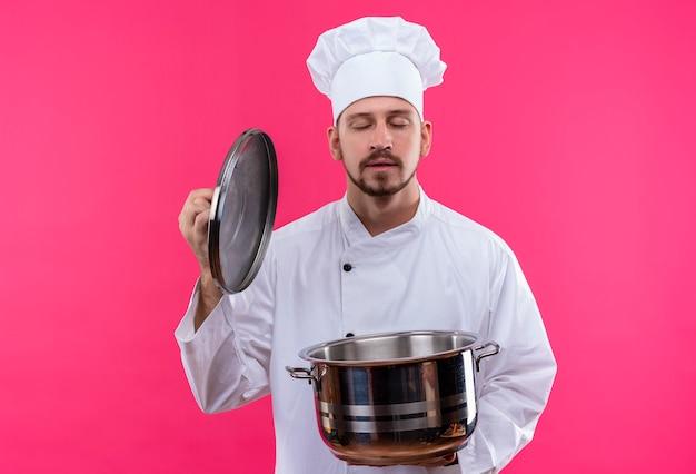 白い制服を着たプロの男性シェフが調理し、パンをかざして帽子をかぶってピンクの背景の上に立って食べ物の心地よい香りを吸い込む 無料写真