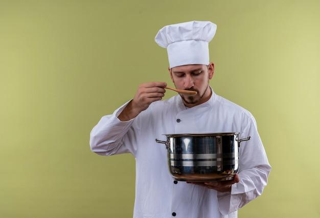 白い制服を着たプロの男性シェフが調理し、鍋を緑の背景の上に立って鍋の味見のパンを保持している帽子を調理します。 無料写真