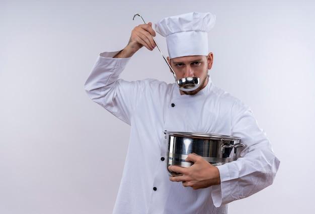 白い制服を着たプロの男性シェフが調理し、白い背景の上に立っている鍋と鍋の味見食品を保持している帽子を調理します。 無料写真