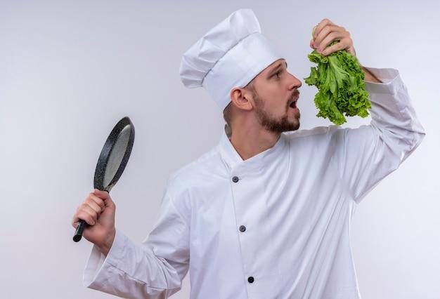 Профессиональный шеф-повар-мужчина в белой форме и поварской шляпе держит сковороду и свежий салат, пытаясь почувствовать его запах, стоя на белом фоне Бесплатные Фотографии