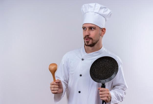 Профессиональный шеф-повар-мужчина в белой форме и поварской шляпе, держащей сковороду и деревянной ложкой, смотрит в сторону счастливым и позитивным положением на белом фоне Бесплатные Фотографии