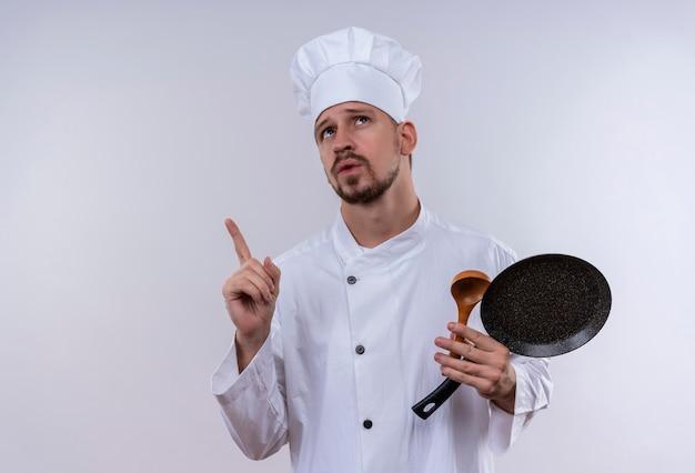 Профессиональный шеф-повар-мужчина в белой форме и поварской шляпе держит сковороду и деревянной ложкой, глядя вверх, указывая пальцем с задумчивым выражением лица, стоя на белом фоне Бесплатные Фотографии