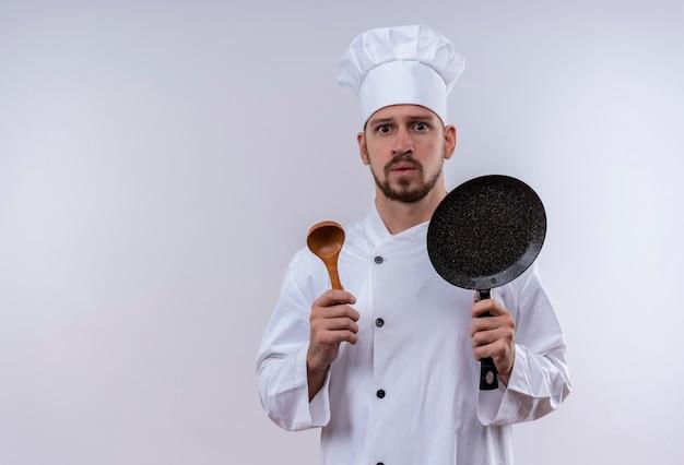 Профессиональный шеф-повар-мужчина в белой форме и поварской шляпе держит сковороду и деревянную ложку, выглядя обеспокоенными, стоя на белом фоне Бесплатные Фотографии