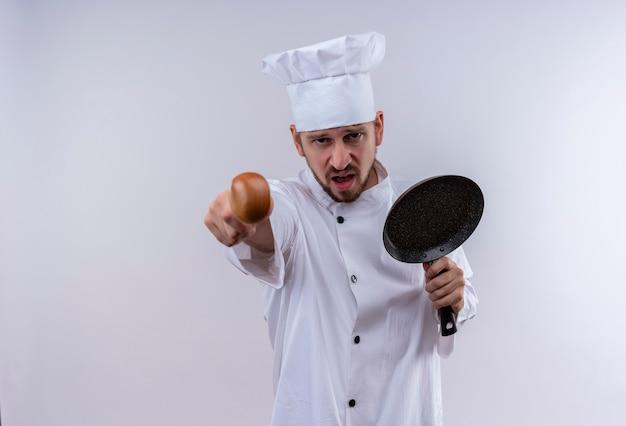 Профессиональный шеф-повар-мужчина в белой форме и поварской шляпе держит сковороду, указывая на камеру с сердитым лицом, стоящим на белом фоне Бесплатные Фотографии