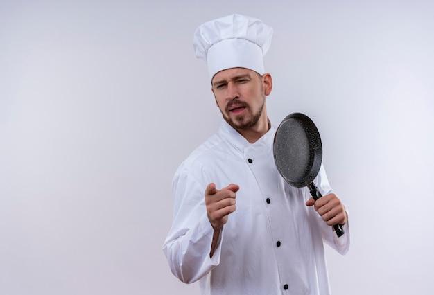 Профессиональный шеф-повар-мужчина в белой униформе и поварской шляпе держит сковороду, указывая на камеру с уверенным взглядом, стоя на белом фоне Бесплатные Фотографии