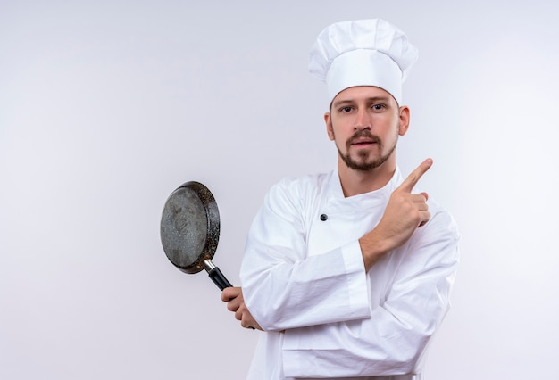 Профессиональный шеф-повар-мужчина в белой форме и поварской шляпе держит сковороду, указывая пальцем в сторону, уверенно глядя, стоя на белом фоне Бесплатные Фотографии
