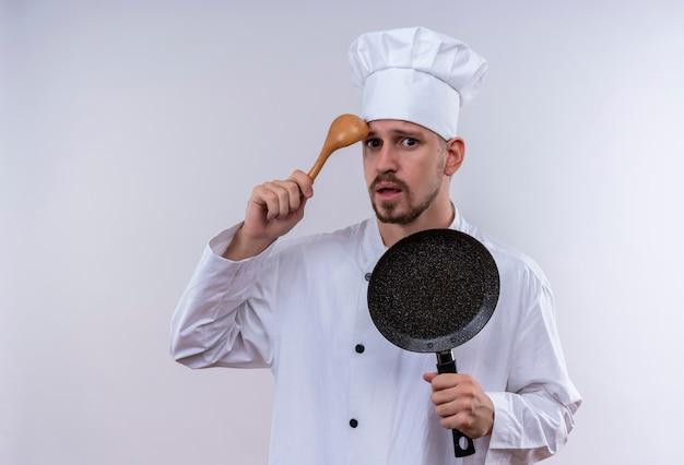 Профессиональный шеф-повар-мужчина в белой форме и поварской шляпе держит сковороду, почесывая голову деревянной ложкой, выглядит смущенной, стоя на белом фоне Бесплатные Фотографии