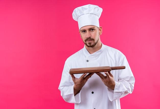 白い制服を着たプロの男性シェフが調理し、ピンクの背景の上に自信を持って立っている木製のまな板を保持している帽子を調理します。 無料写真