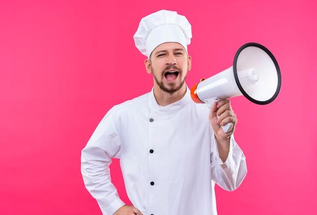 白い制服を着たプロの男性シェフが調理し、ピンク色の背景の上に立ってメガホンに叫んで帽子を調理します。 無料写真