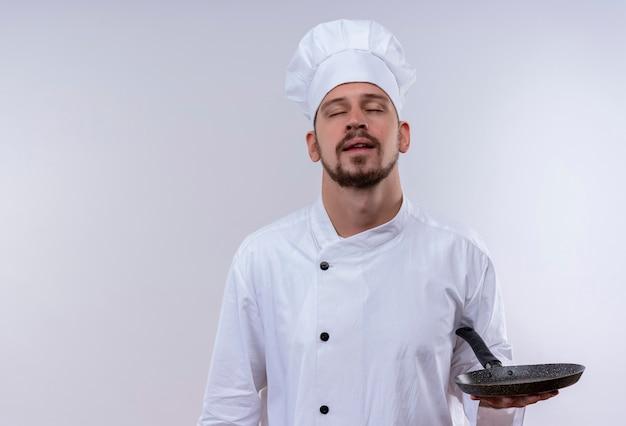 Профессиональный шеф-повар-мужчина в белой форме и поварской шляпе, стоя с закрытыми глазами, держа сковороду на белом фоне Бесплатные Фотографии