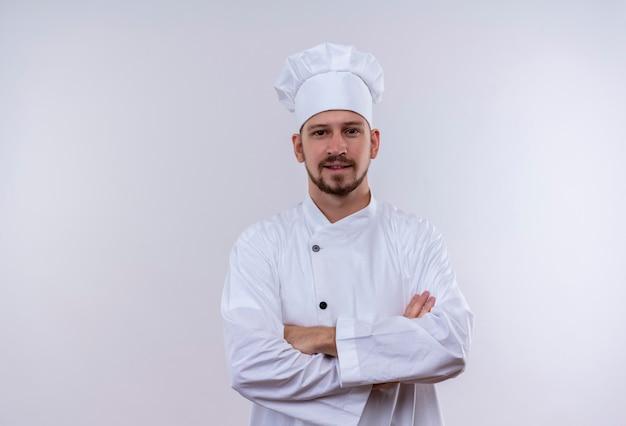 プロの男性シェフが白い制服で調理し、腕を組んで帽子を組んで白い背景に自信を持って立っている笑顔 無料写真