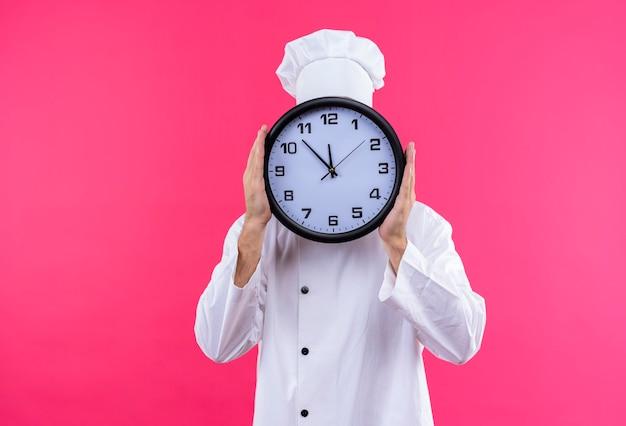 Chef maschio professionista cuoco in uniforme bianca e cappello da cuoco che tiene grande orologio che si nasconde dietro di esso in piedi su sfondo rosa Foto Gratuite