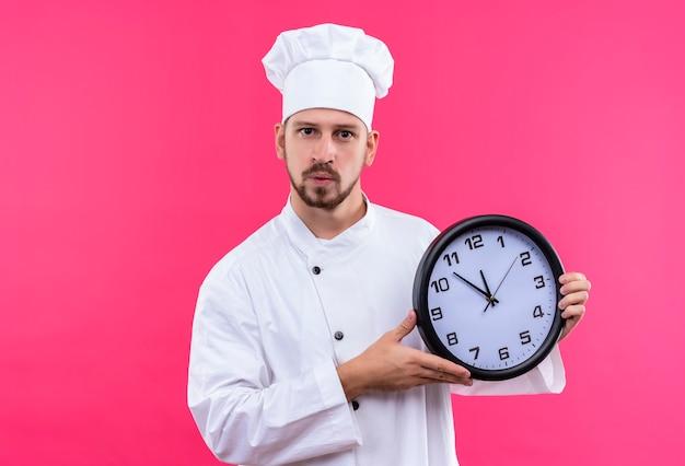 Chef maschio professionista cuoco in uniforme bianca e cappello da cuoco che tiene un orologio che guarda l'obbiettivo con espressione fiduciosa in piedi su sfondo rosa Foto Gratuite