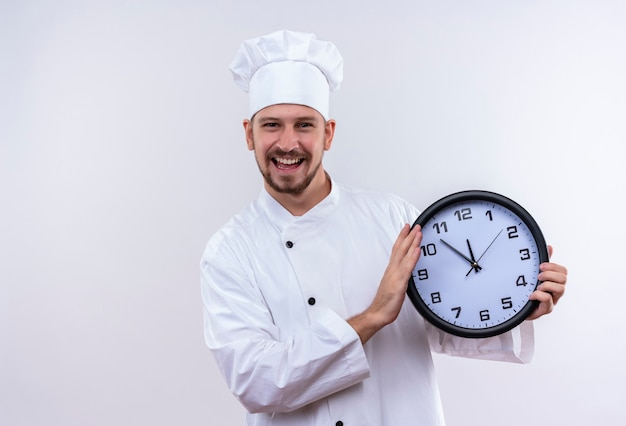 Chef maschio professionista cuoco in uniforme bianca e cappello da cuoco in possesso di un orologio guardando sorridente allegramente in piedi su sfondo bianco Foto Gratuite