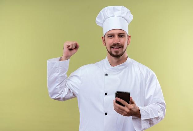 Chef maschio professionista cuoco in uniforme bianca e cappello da cuoco che tiene il telefono cellulare alzando il pugno felice e positivo che si rallegra del suo successo in piedi su sfondo verde Foto Gratuite