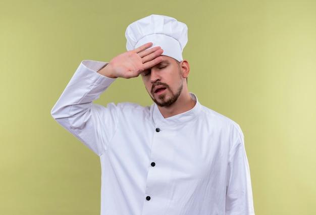 Chef maschio professionista cuoco in uniforme bianca e cappello da cuoco cercando stanco e oberato di lavoro toccando la sua testa in piedi su sfondo gree Foto Gratuite