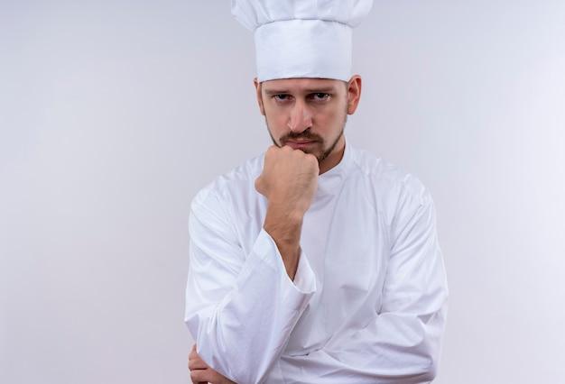 Chef maschio professionista cuoco in uniforme bianca e cappello da cuoco in piedi con il pugno sul mento con espressione pensierosa sul viso su sfondo bianco Foto Gratuite