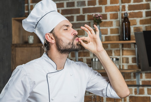 Professional male chef showing sign for delicious Free Photo