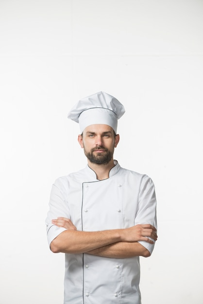 Professional male cook in chef's white uniform standing against white background Free Photo