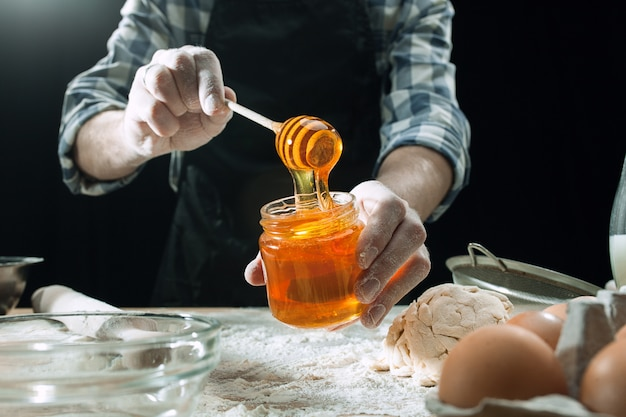 Il cuoco maschio professionista spruzza la pasta con farina, i preapares o cuoce il pane al tavolo da cucina Foto Gratuite
