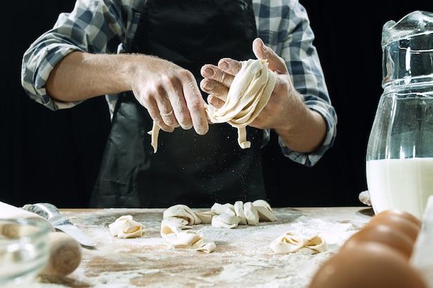 Il cuoco professionista maschio spruzza la pasta con farina, preapares o cuoce il pane al tavolo della cucina Foto Gratuite