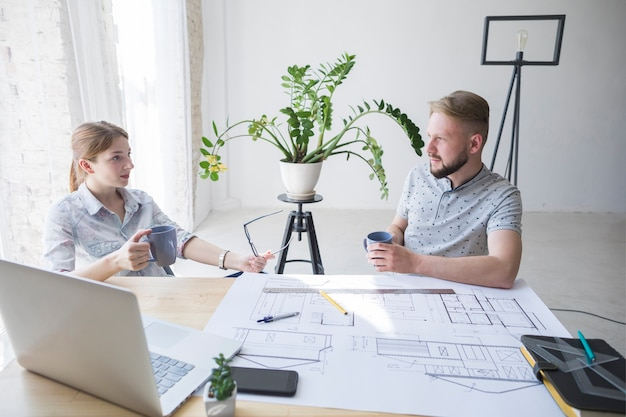 Professional male and female architecture discussing something while coffee break Free Photo