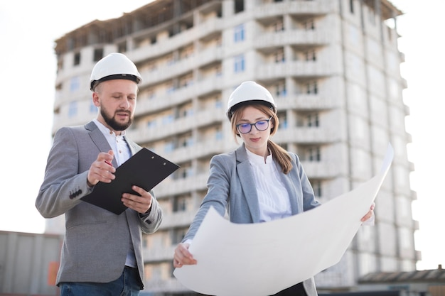 Professional male and female architecture working together at site Free Photo