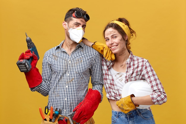 Professional male manual worker wearing protective eyewear on head, mask and gloves holding drilling machine fixing something and his colleague female with dirty face having happy expression Free Photo