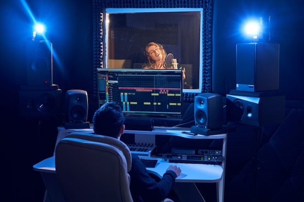 Professional male sound engineer mixing audio in recording studio. music production technology, girl singing into microphone Premium Photo
