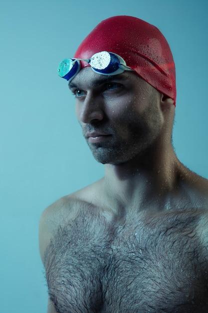 動きと行動、健康的なライフスタイルと動きの帽子とゴーグルを持つプロの男性スイマー 無料写真