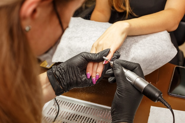 Professional master of manicure makes the nails to the client. Premium Photo