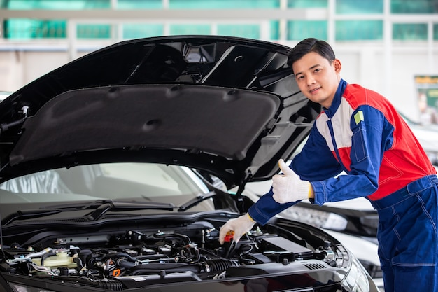 Professional mechanic in uniform is check the quality of ...