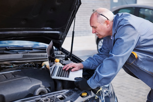 Professional mechanic using contemporary technology at work Free Photo