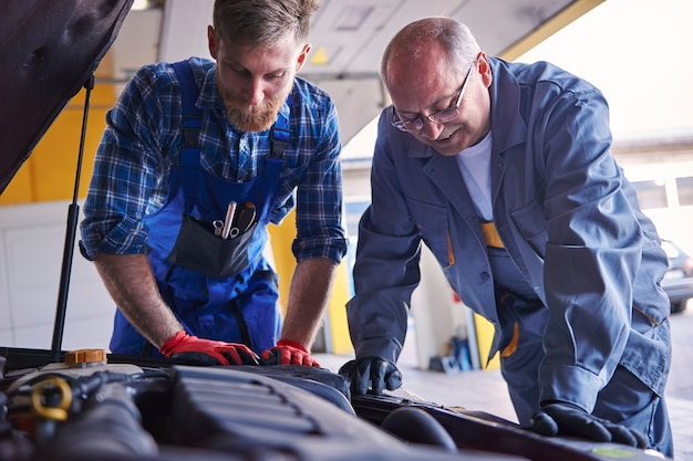 Professional mechanics at popular auto-workshop Free Photo