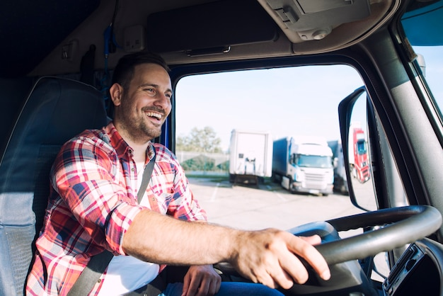 Professional middle aged truck driver in casual clothes driving truck vehicle and delivering cargo to destination Free Photo