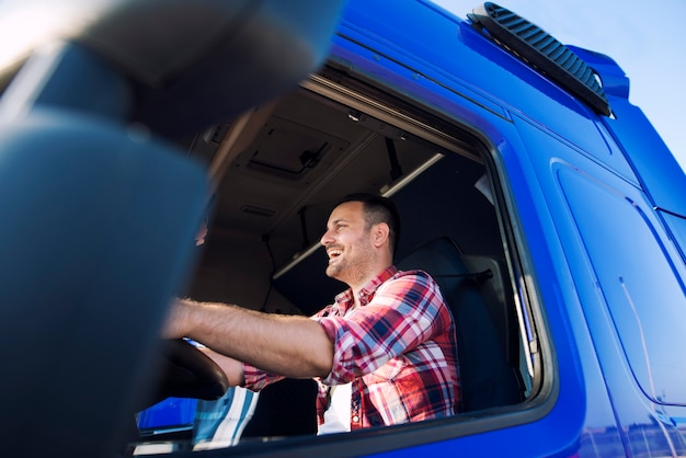 Professional middle aged trucker in cabin driving truck and smiling Free Photo