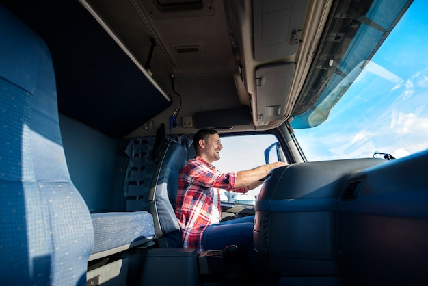Professional middle aged trucker driving truck to the destination Free Photo