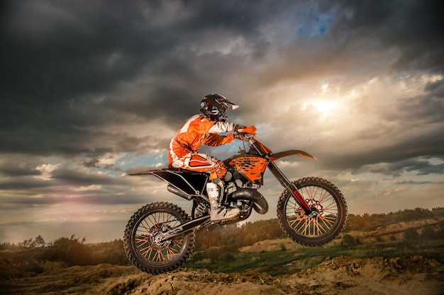 Professional motorcycle rider driving on the mountains and further down the off-road track. it's sunset. Premium Photo
