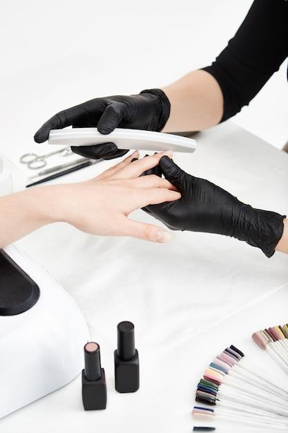 Профессиональный техник ногтя подает ногти перед нанесением лака. Бесплатные Фотографии