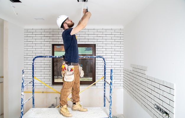 Professional in overalls with tools on the background of the repair site. home renovation concept. Free Photo
