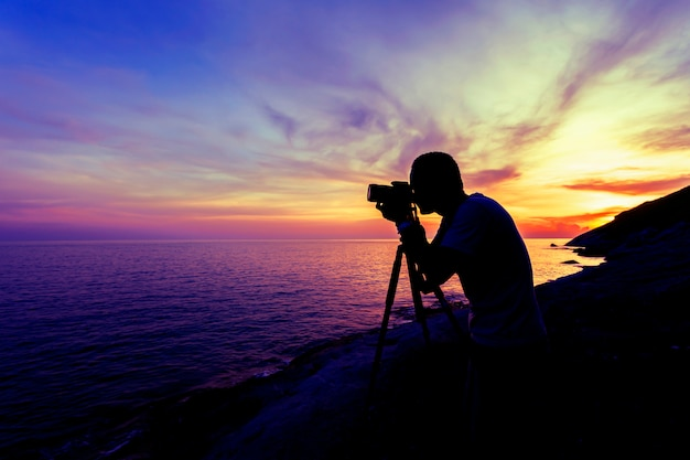 Professional photography man take a photo sunset or sunrise dramatic sky over the tropical sea in phuket thailand Premium Photo