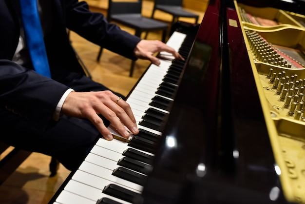 Professional pianist performing a piece on a grand piano. Premium Photo